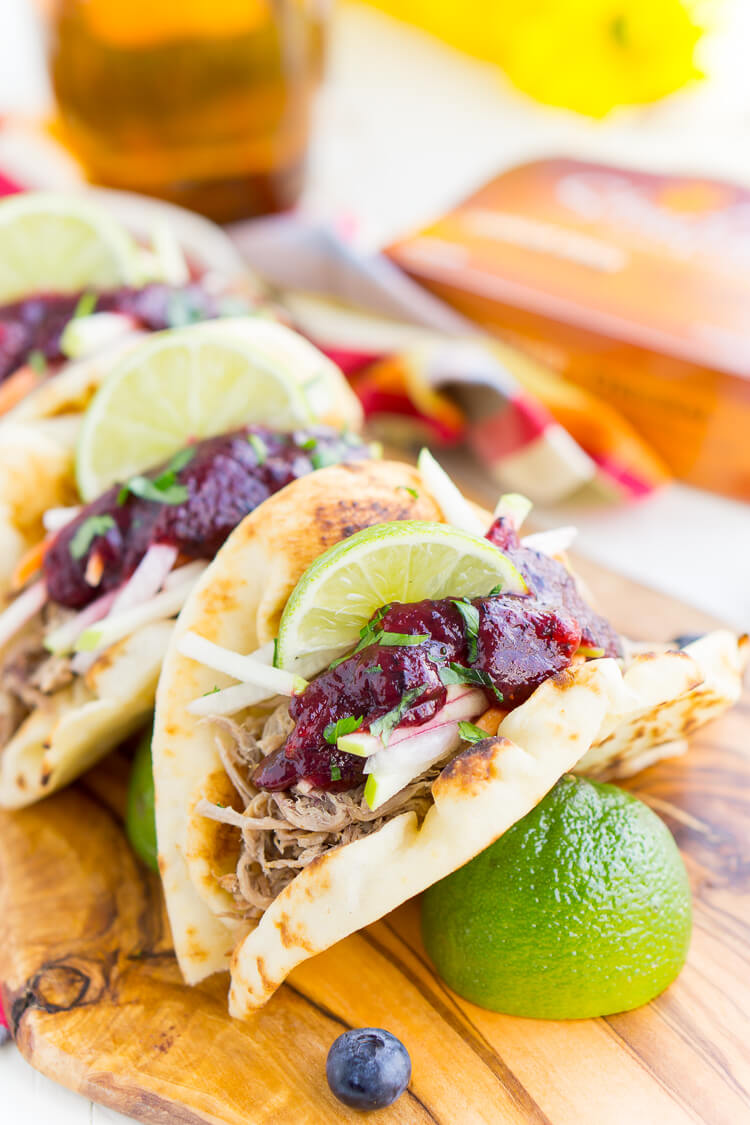 Pulled Pork Tacos with Blueberry Barbecue Sauce are perfect for game days and weeknights! A pork shoulder is slow cooked in root beer, topped with an apple slaw and homemade blueberry barbecue sauce all nestled in delicious naan bread!