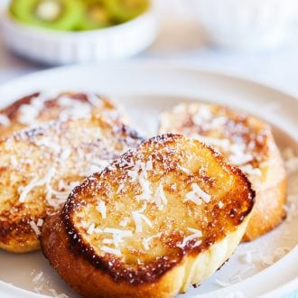 This Coconut French Toast is an easy breakfast that's served with an addictively delicious and creamy coconut syrup made with butter, buttermilk, sugar, and coconut extract!