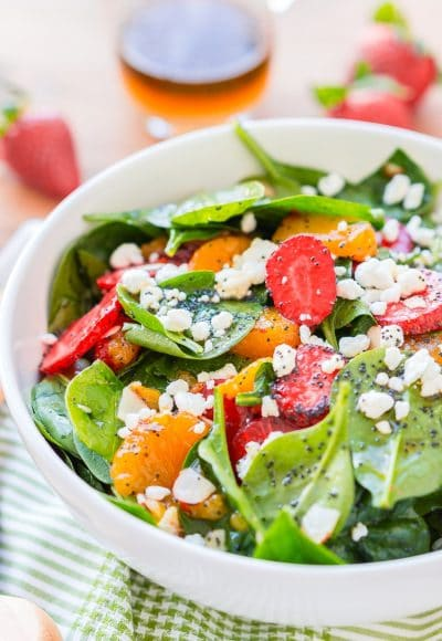 This Strawberry Spinach Salad will become your new go-to recipe for summer, it's made with simple, flavorful ingredients like goat cheese, almonds, poppyseeds, strawberries, mandarins, and spinach, and you can make it family or party-sized!