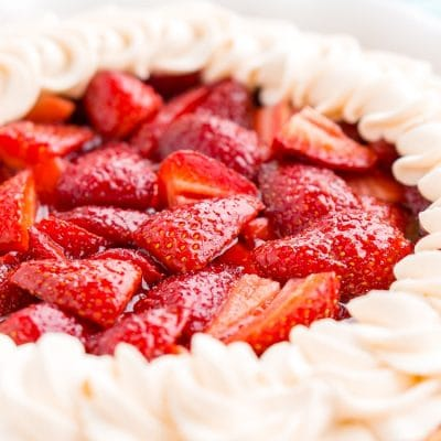 Close up photo of strawberry pie made with jello and topped with whipped cream.
