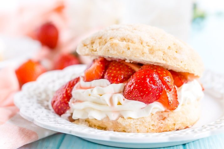 White plate with strawberry shortcake made with a biscuit, whipped cream, and macerated strawberries on it.