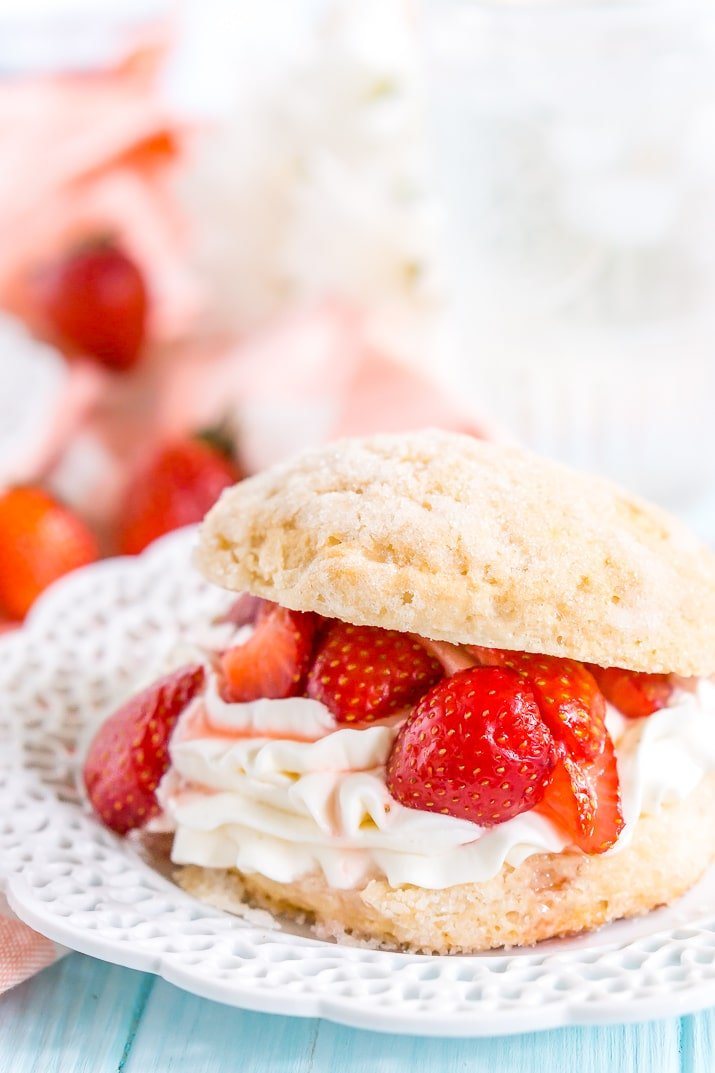 Close up photo of a prepared strawberry shortcake dessert on a white plat with more strawberries in the background.