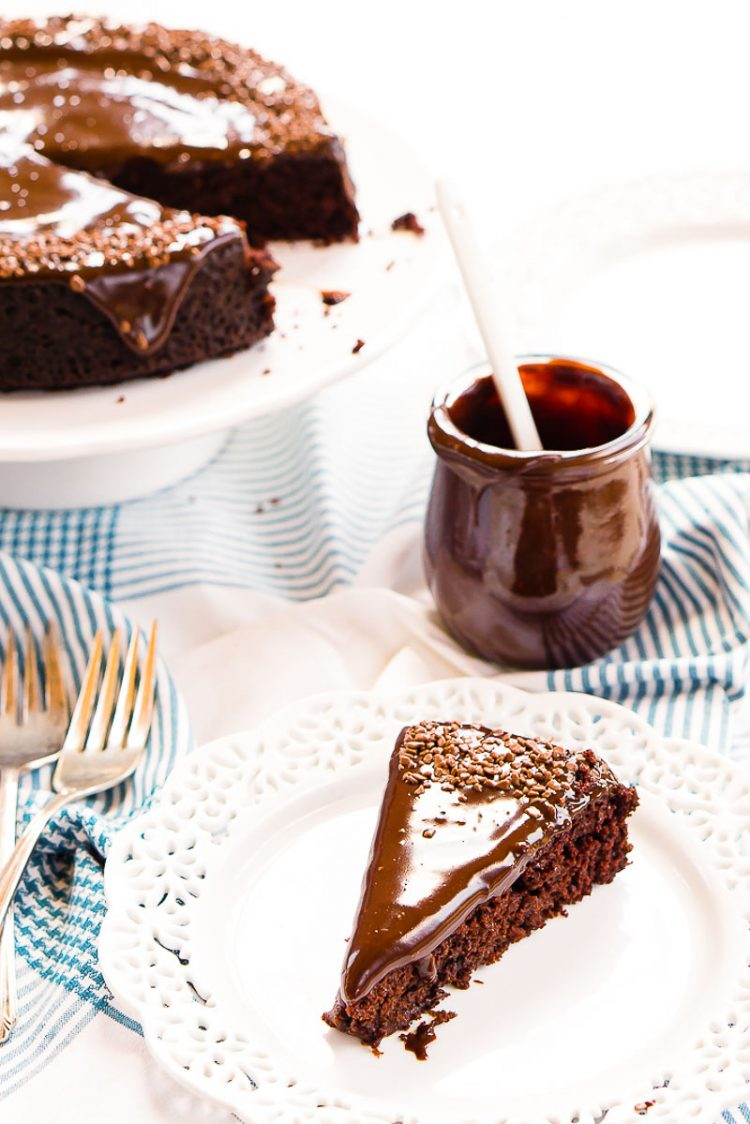 Slice of chocolate depression cake on a white plate with a jar of icing and the rest of the cake on a cake stand behind it.