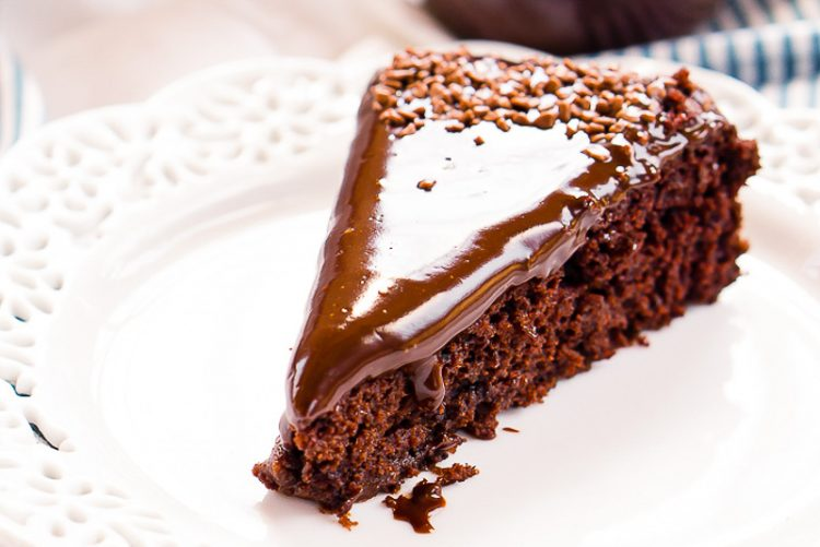 Slice of chocolate wacky cake on a white plate.