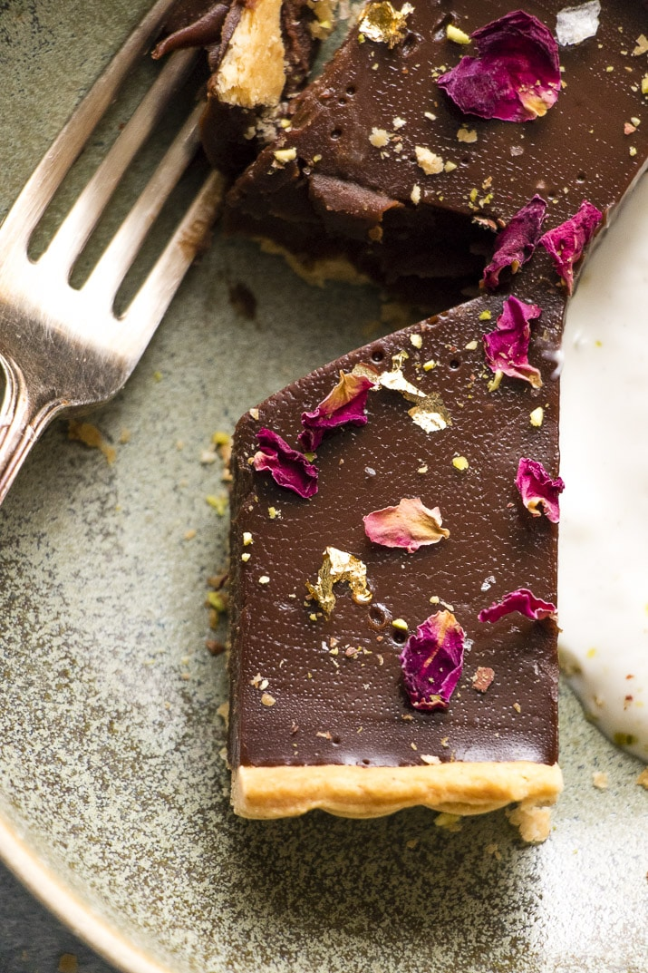 This is the creamiest dreamiest chocolate truffle tart that you will ever eat. Dark smooth chocolate, in a crispy flaky crust, topped with hazelnuts, pistachios and rose petals... and a little gold make this the perfect indulgent treat for any occasion.