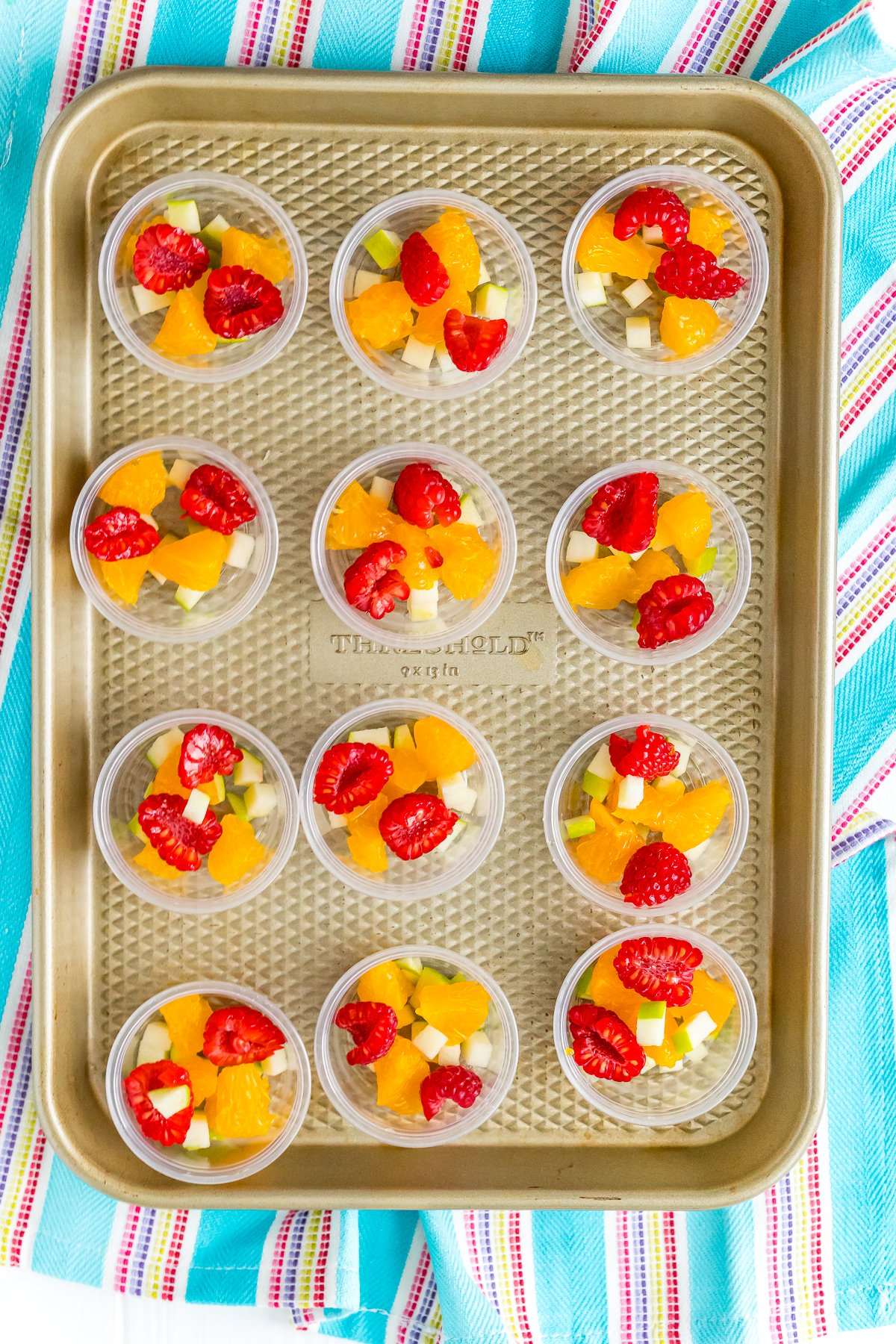 Jello shot cups filled with fruit on a baking sheet.