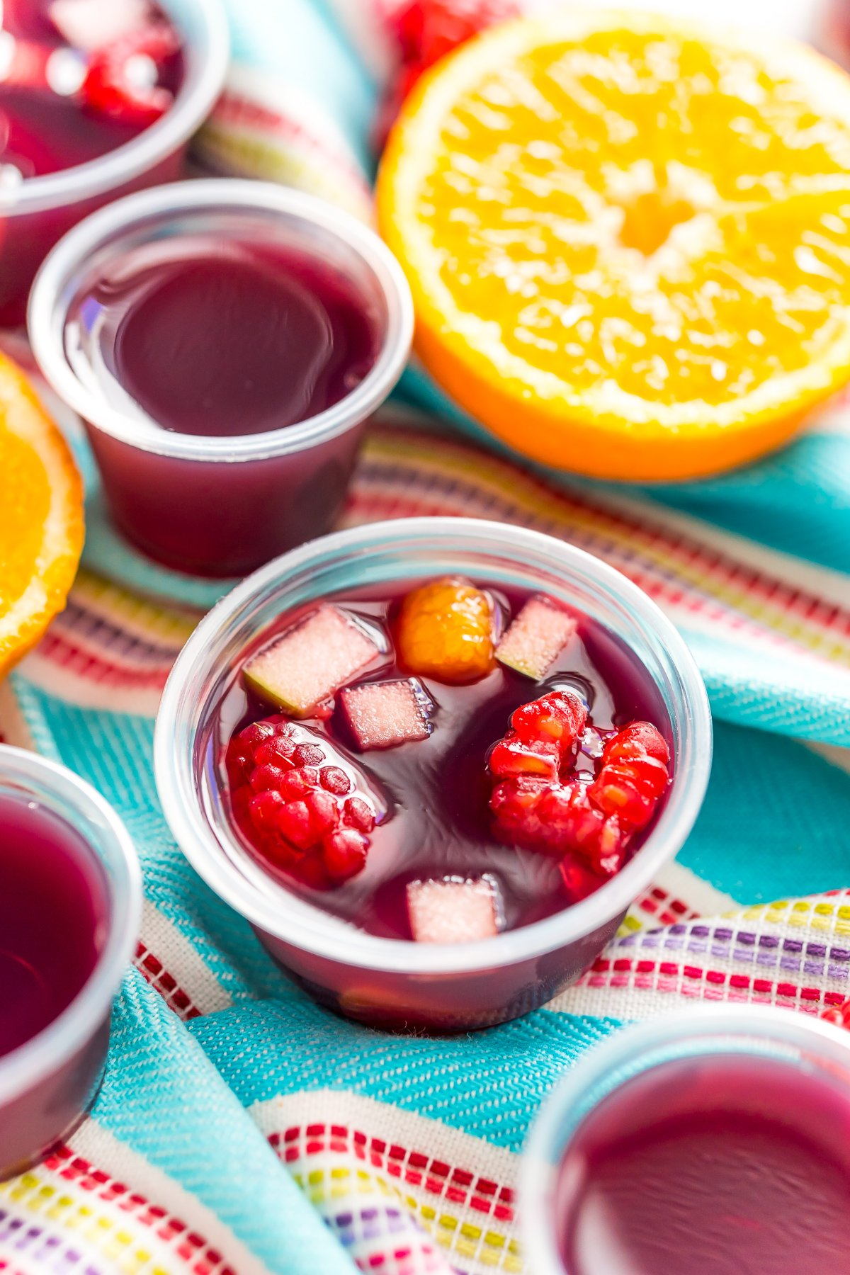 Sangria jello shots on a blue striped napkin with more jello shots and fruit scattered around.
