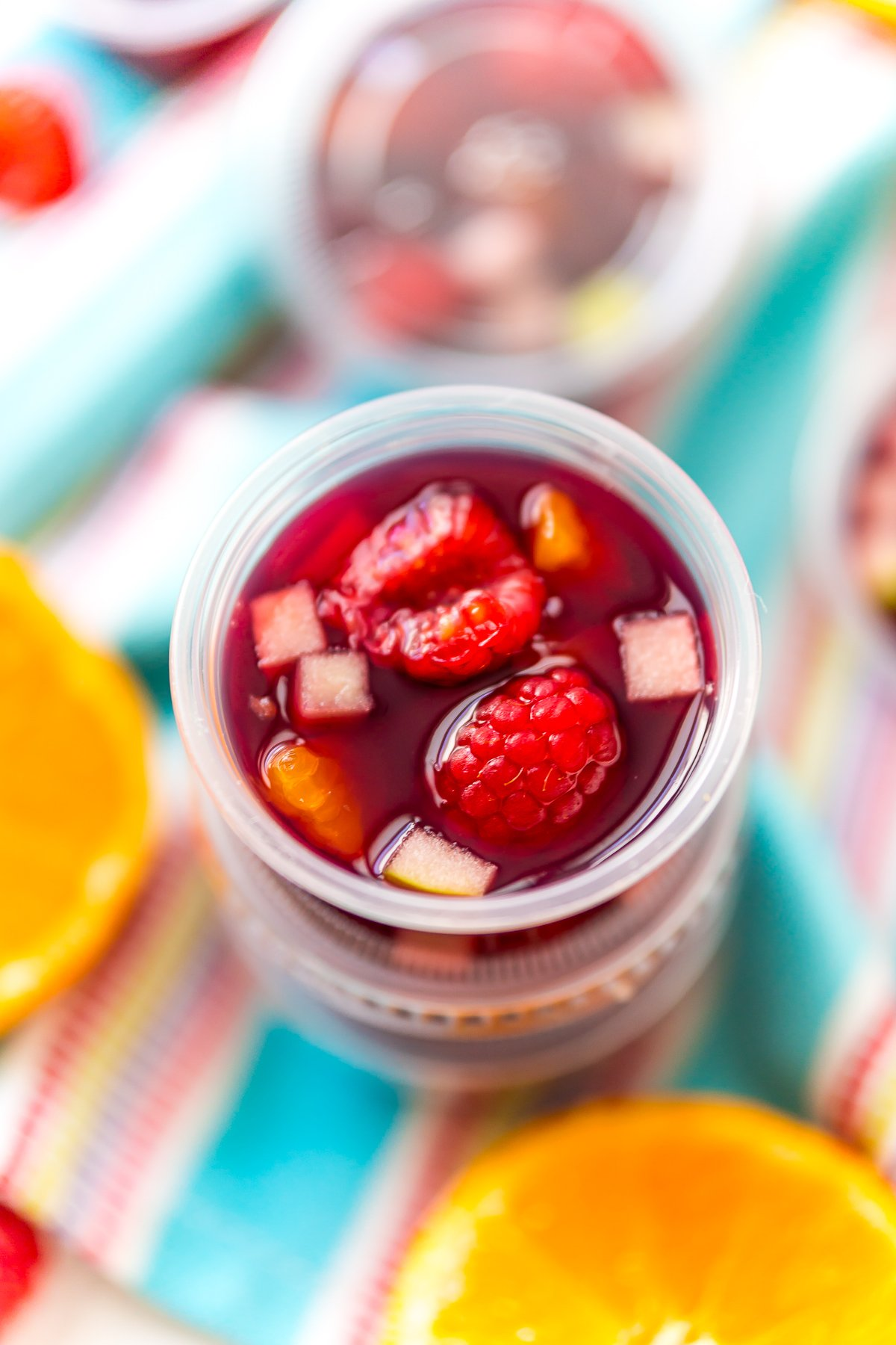 Sangria Jello Shots stacked on top of each other on a blue napkin with fruit scattered around.