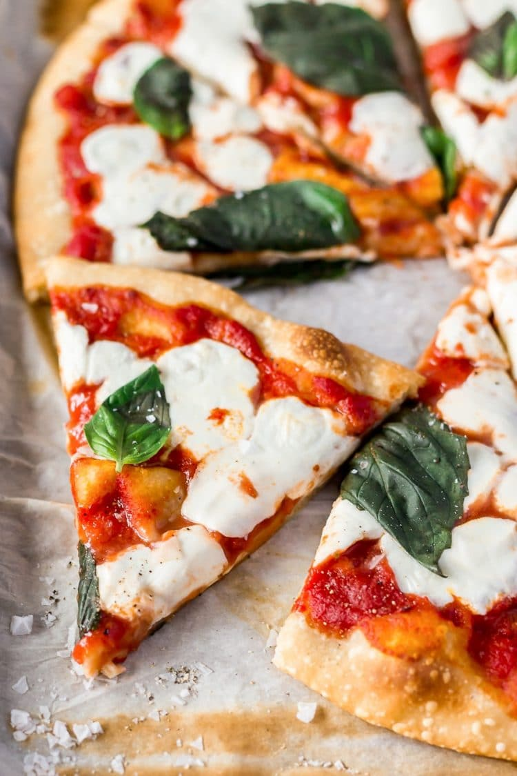 A Classic Margherita Pizza made with delicious dough, olive oil, crushed tomatoes, garlic, mozzarella, and basil always hits the spot when you need a quick and easy dinner recipe!