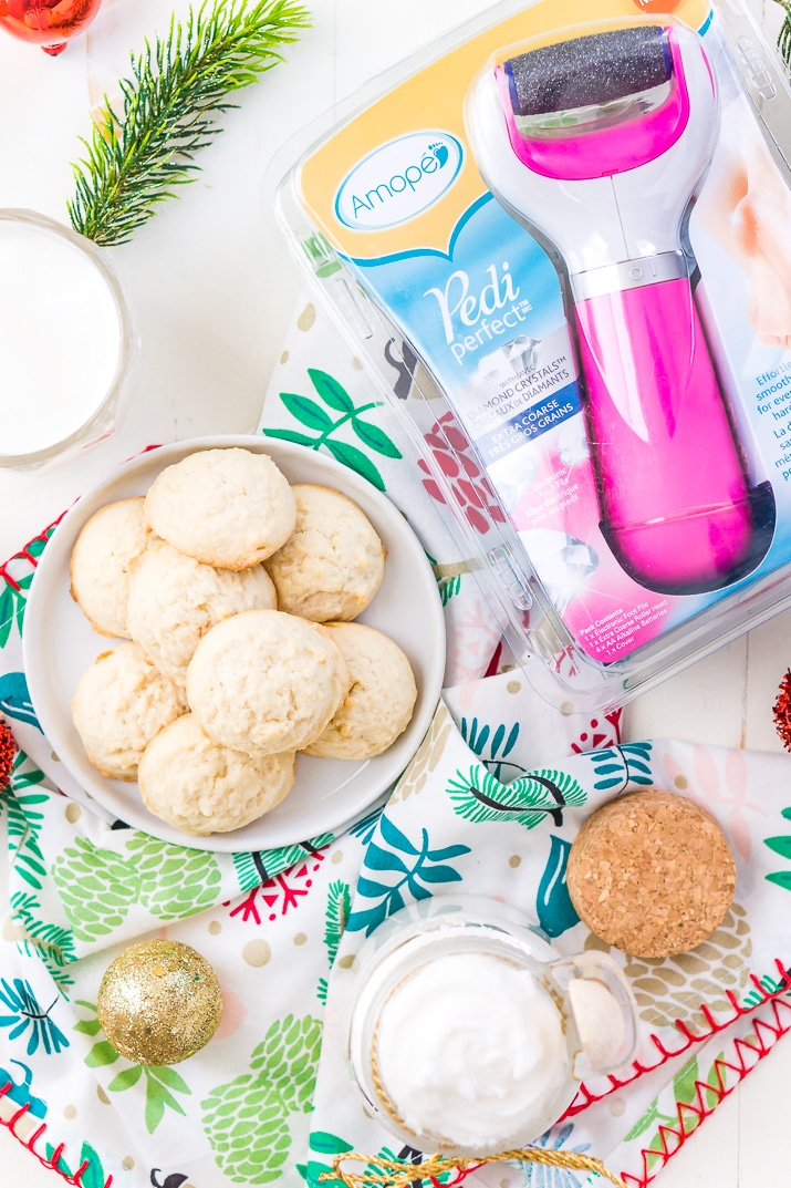 This Sugar Cookie Body Scrub is made with sugar, coconut oil, and fragrance oil. You'll love how easily this 3-ingredient DIY gift comes together! Add it to a holiday gift basket with an Amopé Pedi Perfect Foot File, slippers, nail polish, and chocolate for a fun foot spa-themed gift!