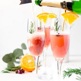 This Cranberry Orange Mimosa is the perfect cocktail for winter brunch! Made with cranberry and orange juice and champagne it's a fruity drink that you can serve up for Christmas or New Year's Eve or any other weekend celebration!