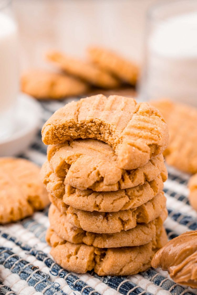 A stack of peanut butter cookies with the top cookie missing a bite on a striped napkin with more cookies and milk in the background.