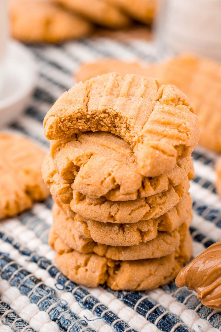Close up photo of peanut butter cookies stacked on a striped napkin.