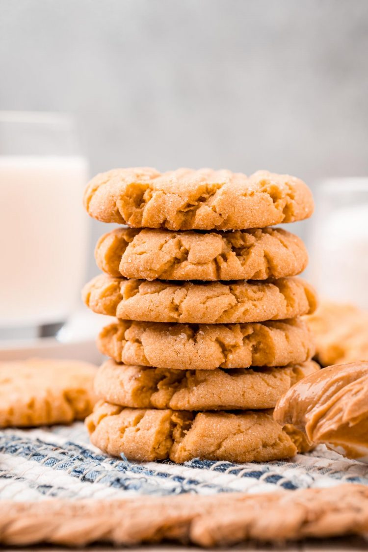 Straight on shot of a stack of 6 peanut butter cookies on a striped placemat.