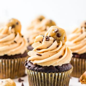 Chocolate cupcakes topped with peanut butter frosting and a mini cookie on a white cake stand.