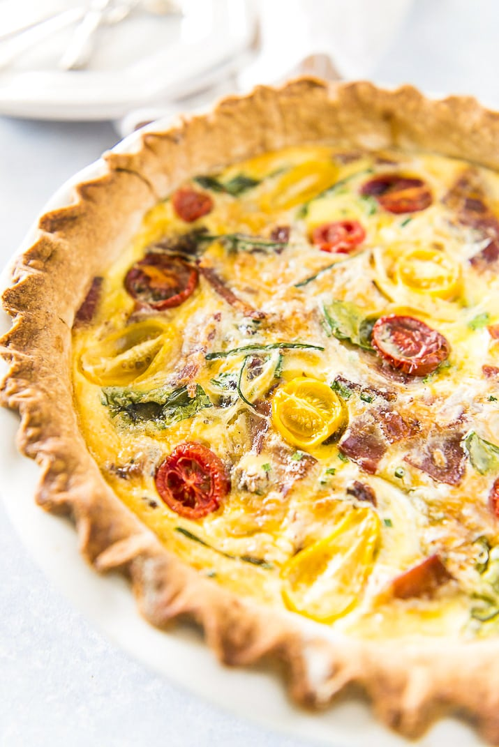 Whole Quiche Lorraine made with bacon, onion, spinach, tomatoes and more in pie dish.