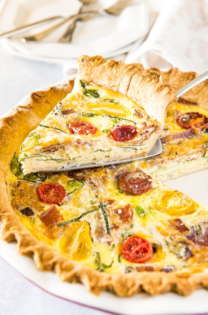 Slice of bacon spinach quiche lorraine on pie server