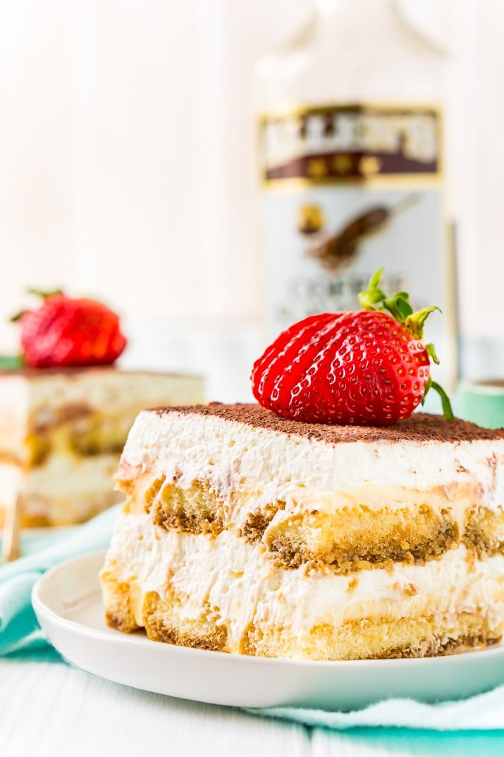 Tiramisu on Plate with Coffee Liqueur Bottle and Strawberry