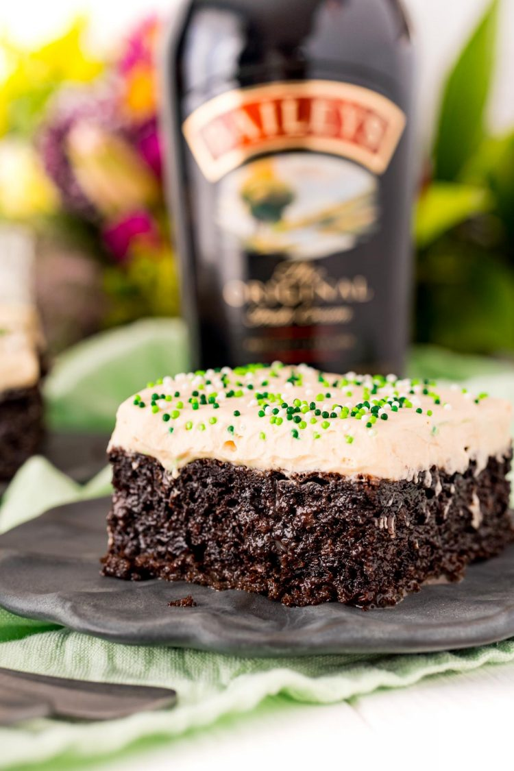 Close up photo of Irish Cream Cake on a black plate with a bottle of Bailey's in the background.