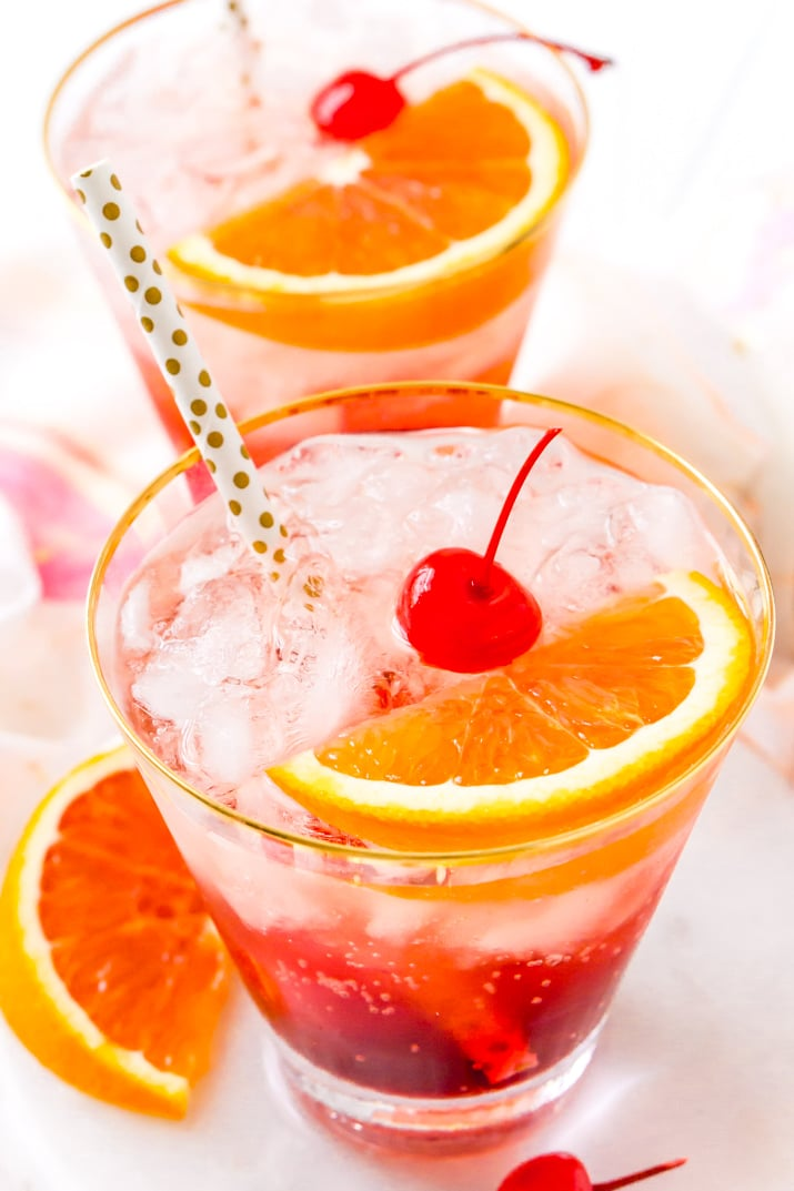 Close up photo of a shirley temple drink garnished with maraschino cherries and orange slices.