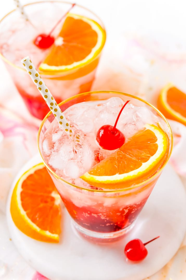 Two glasses filled with shirley temple drinks with gold polka dot straws and cherries and orange slices in them.