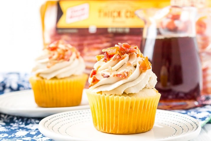 Maple Bacon Cupcakes on plate with syrup dispenser and package of bacon