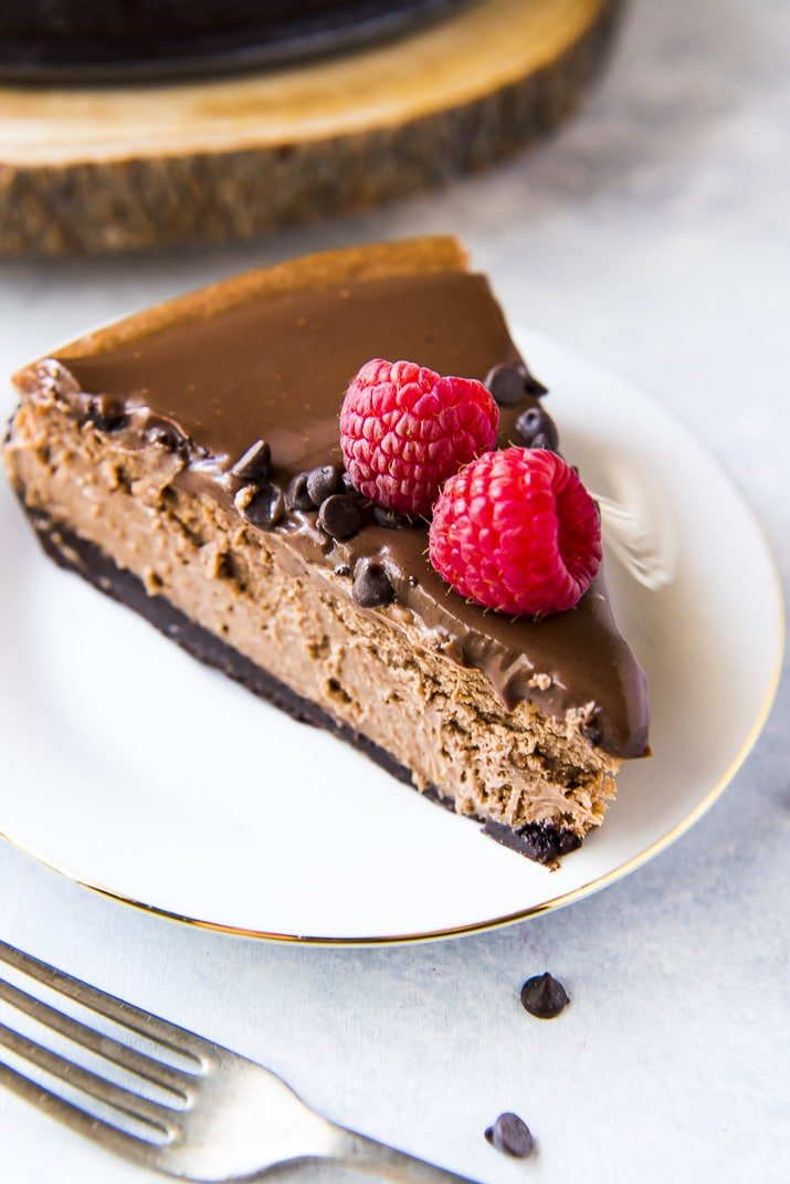 Chocolate cheesecake recipe with raspberries on white plate