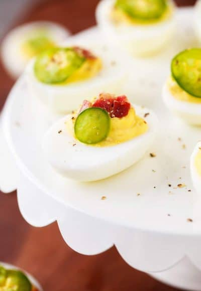 Spicy Deviled Eggs are made with mayo, mustard, relish, sriracha, jalapeño, and bacon. This easy recipe is the perfect snack to serve at summertime barbecues and cookouts!