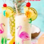 Glass with a flamingo painted on it with a pina colada in it topped with a drink umbrella and pineapple wedge.