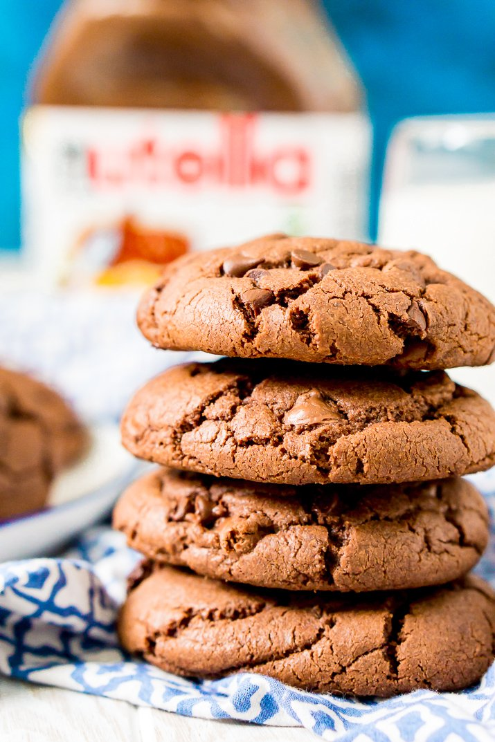 Close up photo of a stack of Nutella stuffed chocolate cookies on a blue and white napkin.