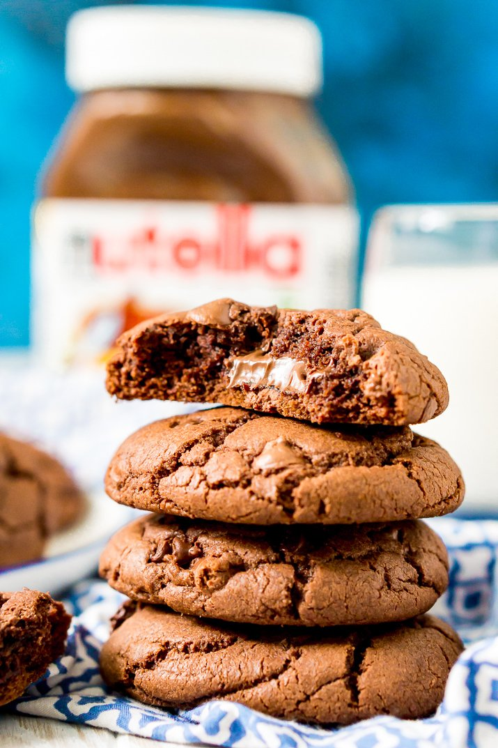 Close up photo of a stack of 4 chocolate cookies on a blue and white napkin, the top one has a bite taken out of it revealing nutella.