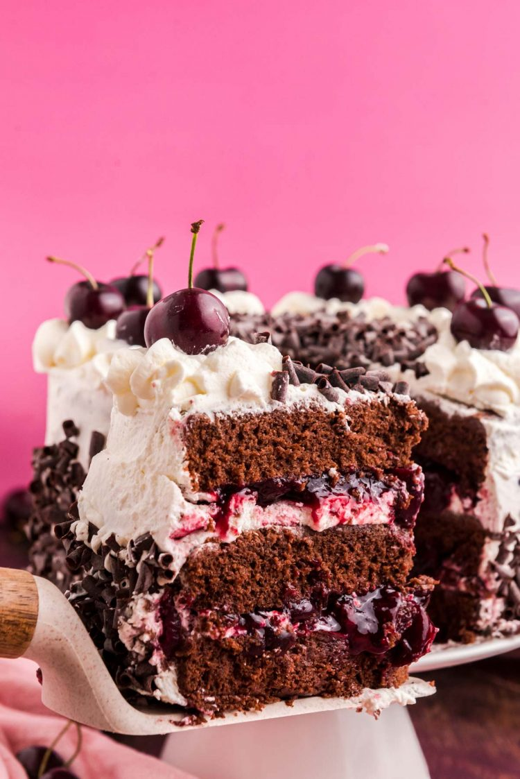 Close up photo of a slice of black forest cake on a cake server being pulled away from the rest of the cake.