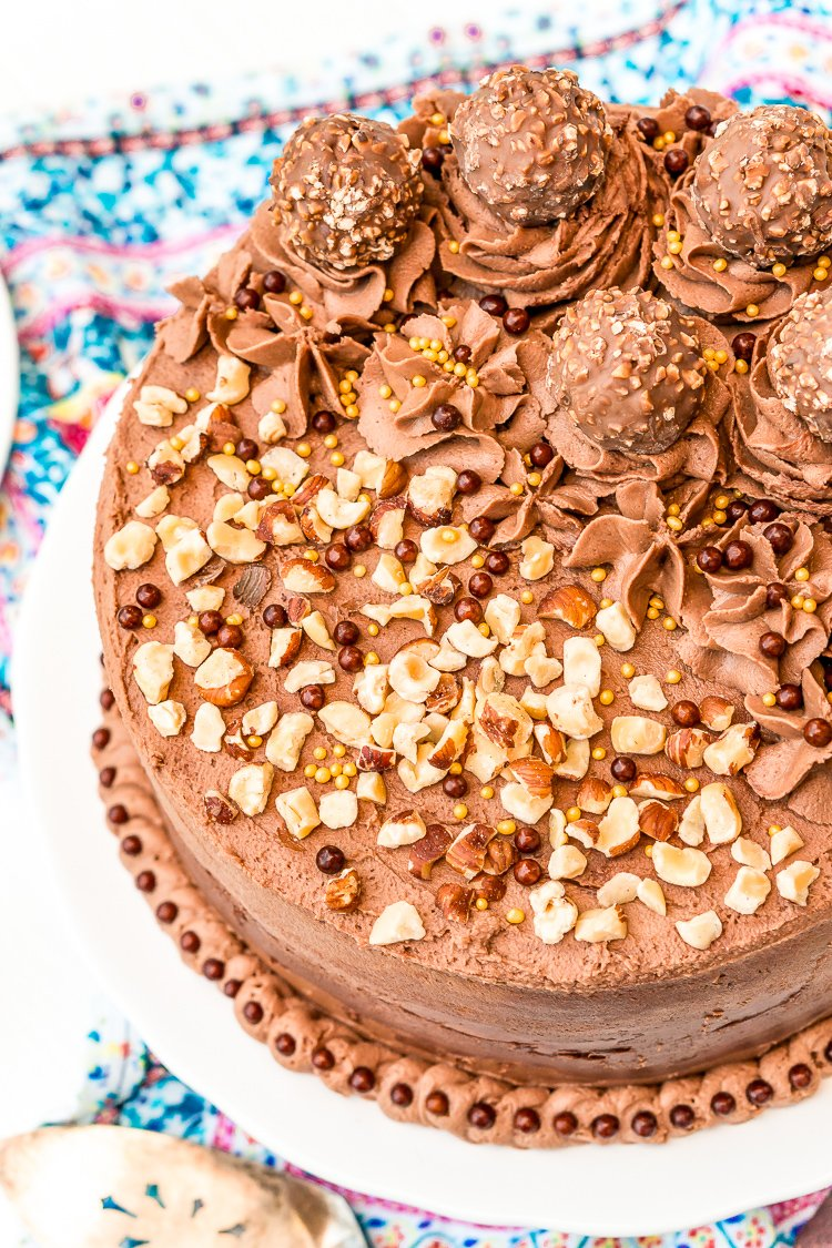 Nutella hazelnut cake on a cake stand topped with Ferrero Rocher candy and chopped hazelnuts.