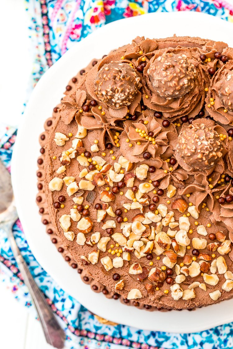Photo of the top of a chocolate cake topped with chopped hazelnuts and Ferrero Rocher candy.