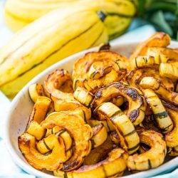 Delicata Squash is a small, easy to cook squash that's sweet and tender and doesn't require peeling because you can eat the skin! Roast it with salt, pepper, and olive oil or cinnamon, brown sugar, and coconut oil for an even sweeter side dish!