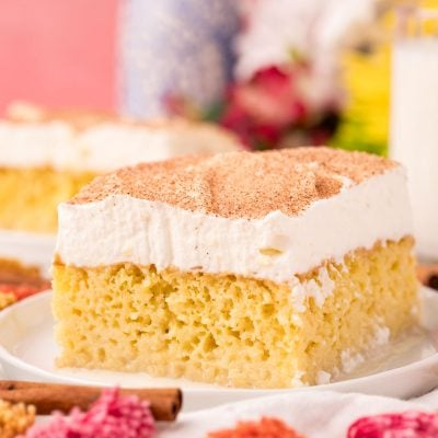 Close up photo of a slice of tres leche cake on a white plate.