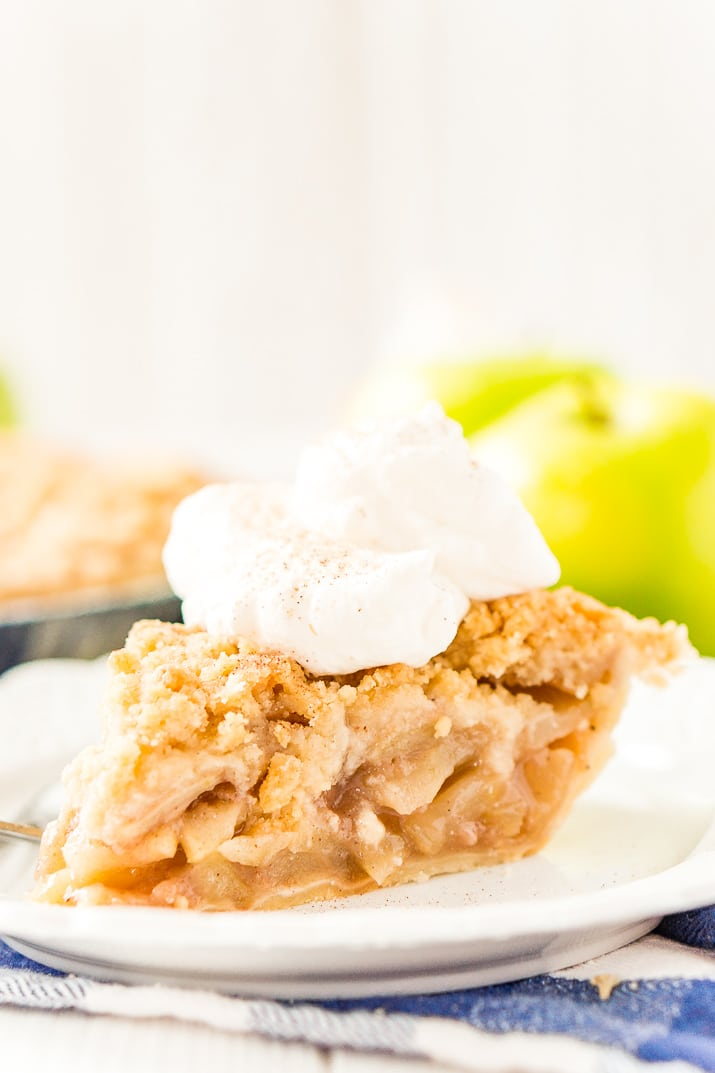 A slice of Dutch Apple Pie on a white plate.