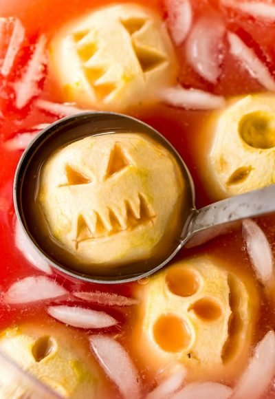 """Shrunken Head Party Punch doubles as a delicious drink and a creepy conversation piece! Made with fruit juices, lemon-lime soda, and a splash of grenadine, the best part of this beverage is the floating """"shrunken heads"""" which are made with baked apples!"""