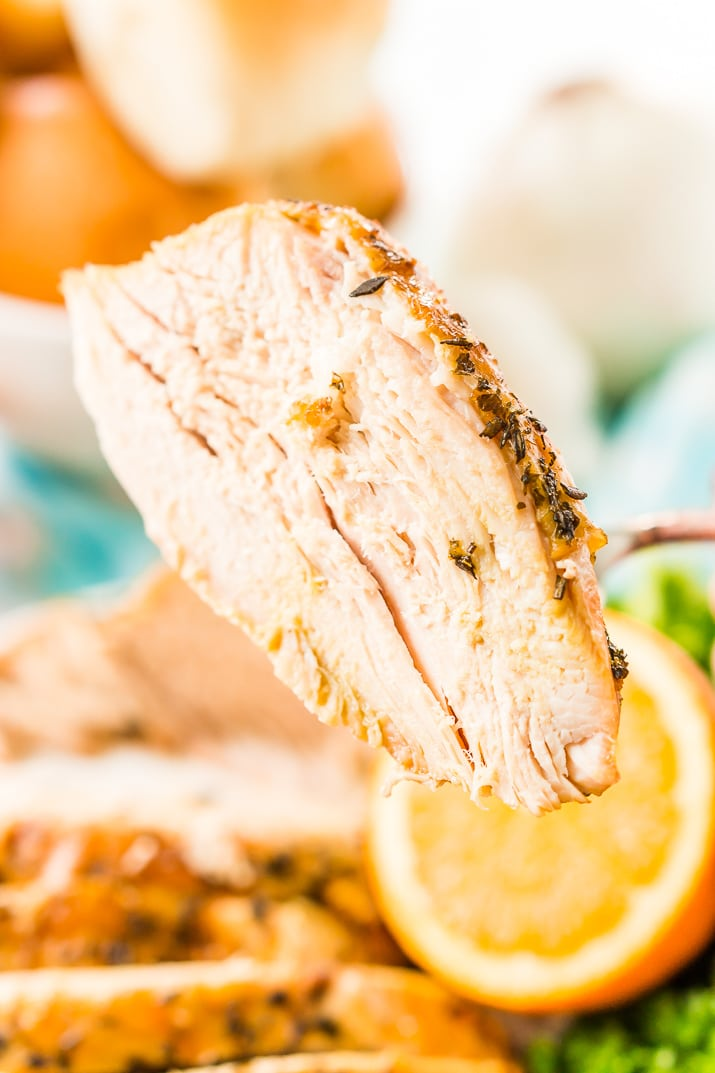 Big slice of turkey breast being held with a fork.