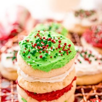 A stack of red, white, and green frosting sugar cookies on a cooling rack surrounded by holiday decorations.