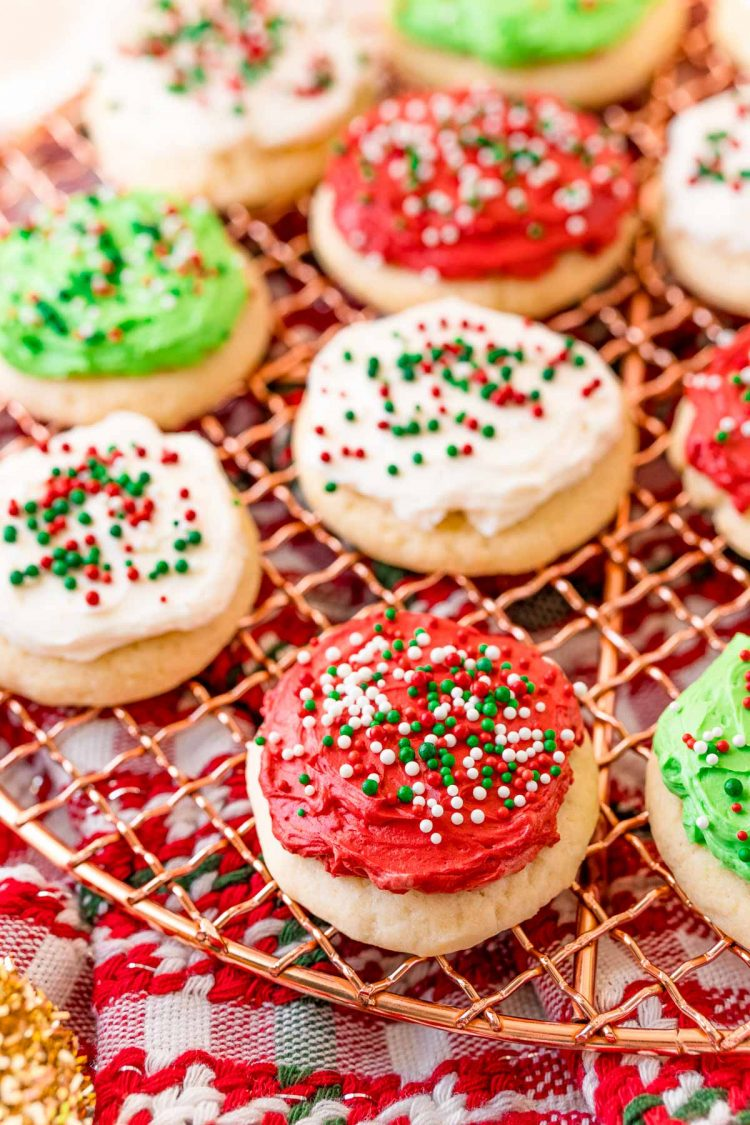 Red, white, and green frosted sugar cookies on a wire cooling rack covered in sprinkles.
