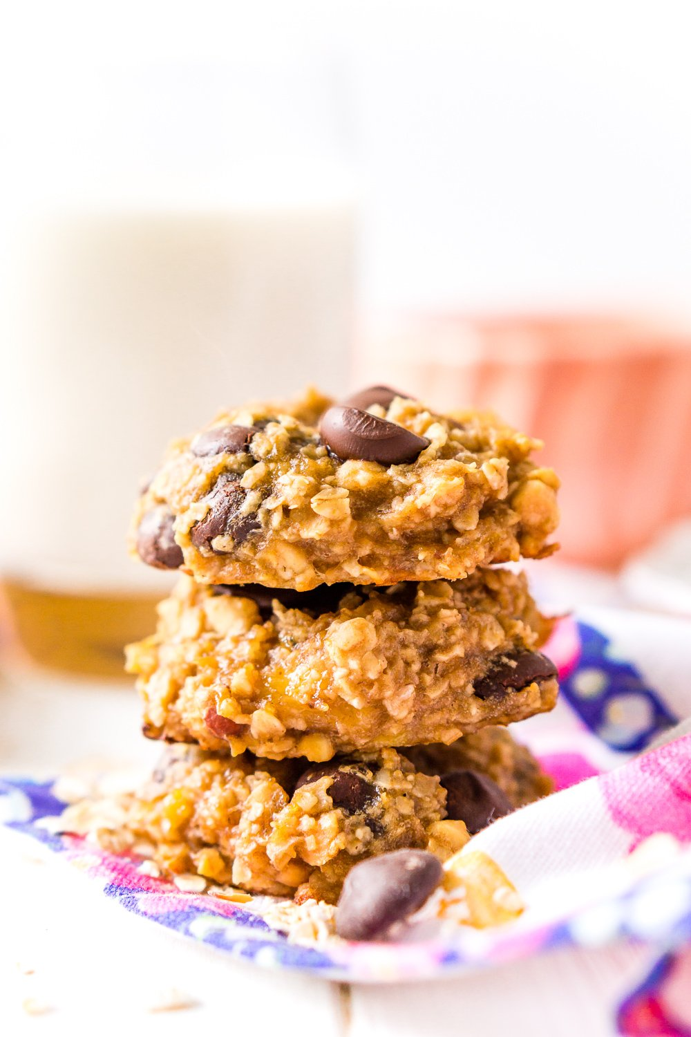 Banana Oatmeal Cookies with chocolate chip stacked three high with milk in background.