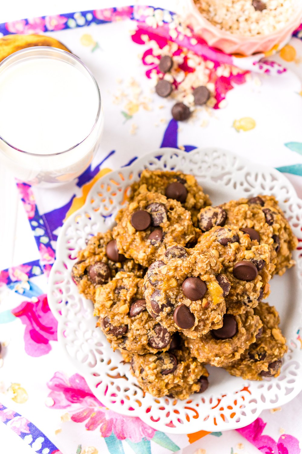 Overhead shot of Banana Chocolate Chip Cookies on white plate with glass of milk.