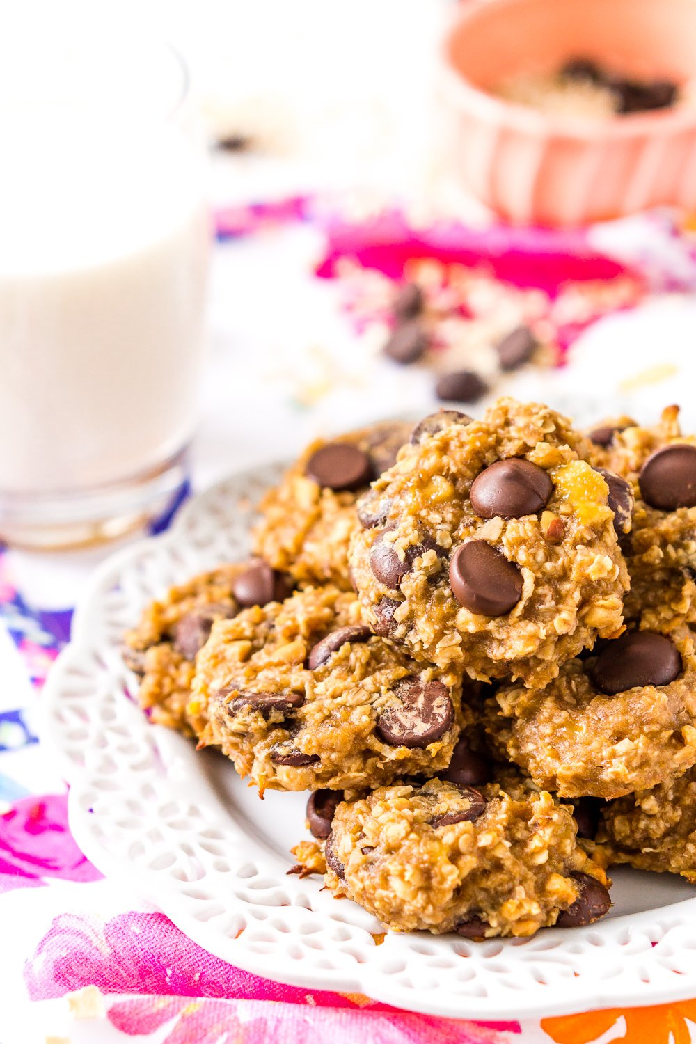 Banana Oatmeal Cookies on white plate on colorful napkin with glass of milk and pink bowl in background