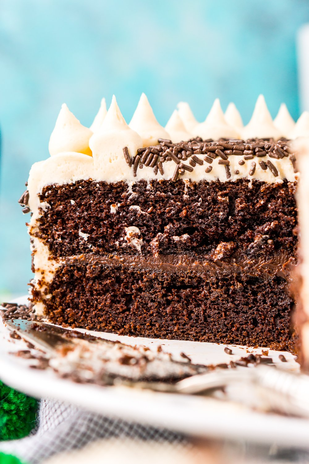 Chocolate Guinness Cake that's been sliced into and you can see the layers of chocolate cake, chocolate ganache, and Irish Cream Buttercream against a blue background.