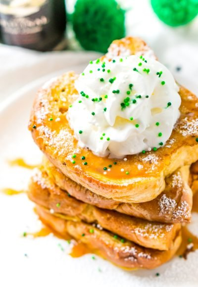 Slightly overhead photo of a stack of Irish Cream French Toast on a white plate with caramel syrup whipped cream and green sprinkles.