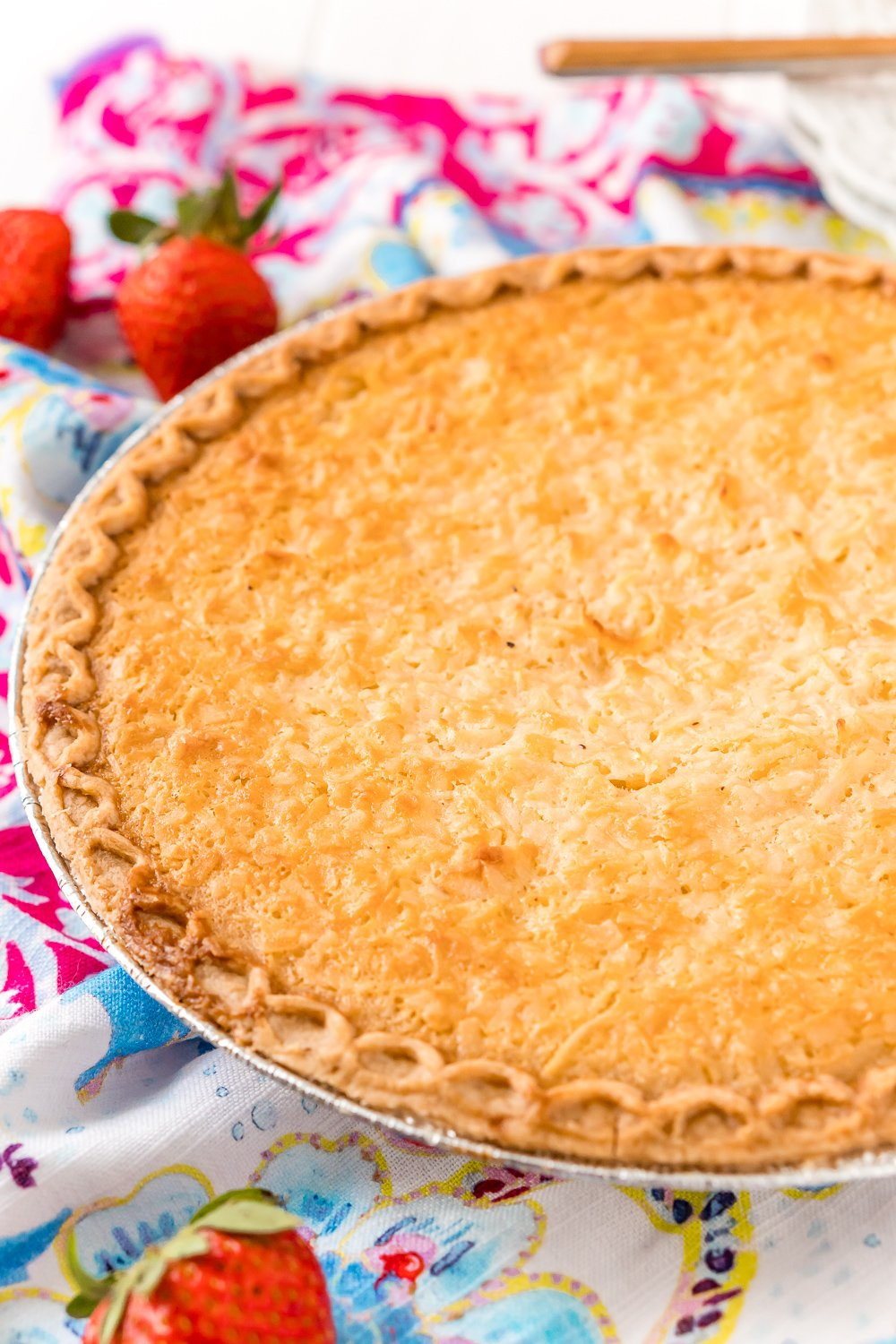 Photo of a Coconut Custard Pie in a pie tin with strawberries scattered around.