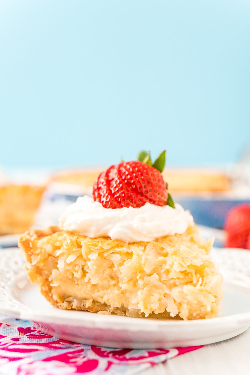 Slice of Coconut Custard Pie on a white plate with pink and white napkin and a blue background. Pie has whipped cream and a strawberry on top.