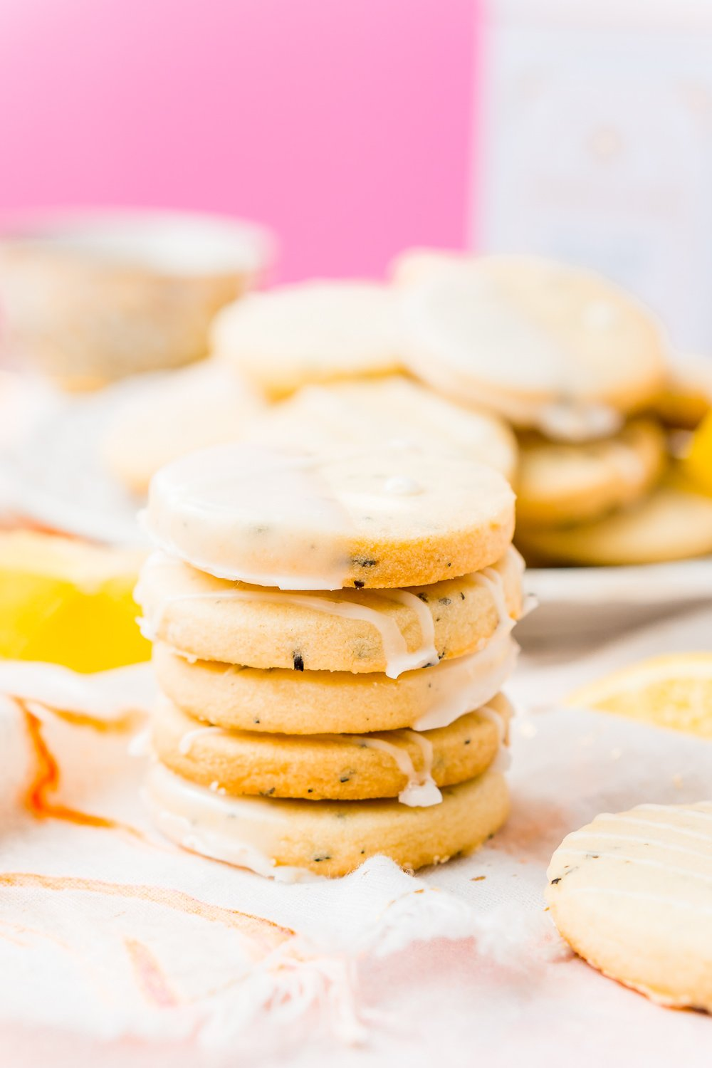 Stack of five Earl Grey Cookies with lemon icing with plate of cookies in the background.