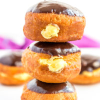 Stack of three Boston Cream Donuts on top of each other, more donuts in background.